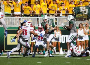 Baylor Bears quarterback Seth Russell (17) sidesteps an attempted tackle by SMU Mustangs linebacker Carlos Carroll (55) for a touchdown during the third quarter at McLane Stadium in Waco, Texas.
